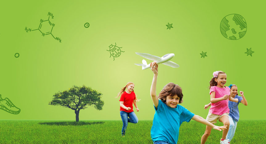 4 kids in a field running with a tree in the background.  one boy in a blue shirt is holding a toy airplane